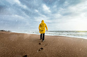 Man on the beach on a rainy day