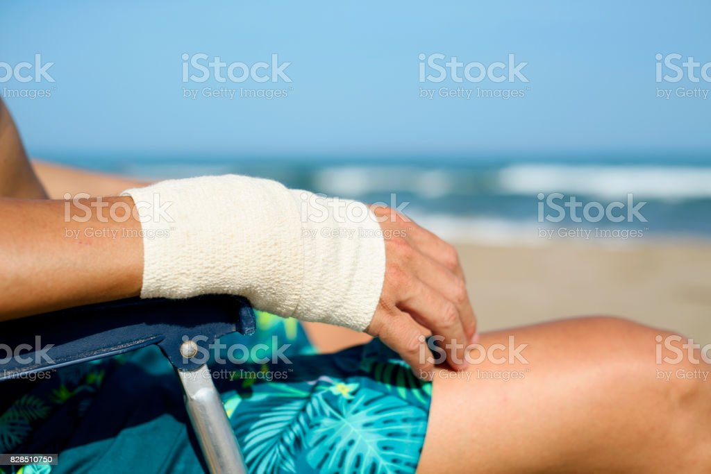 man on the beach with a bandage in his wrist stock photo