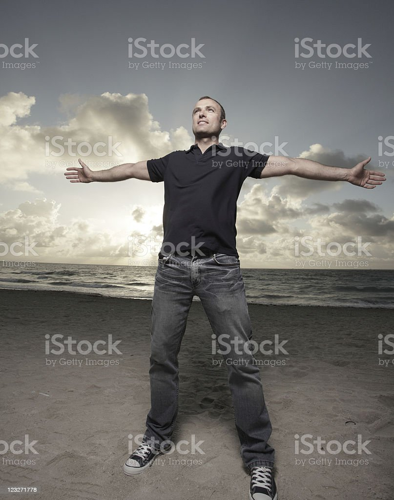 Man on the beach with arms extended outward royalty-free stock photo