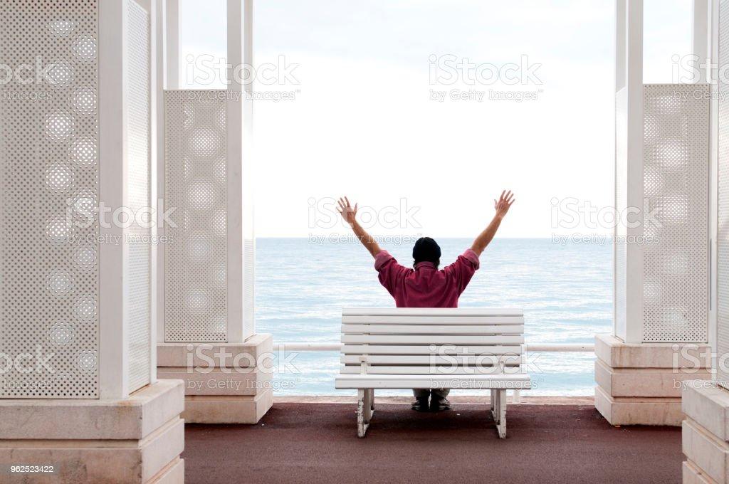 Homem no banco com os braços erguidos - Foto de stock de Acaso royalty-free