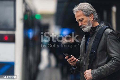 Mature man waiting on the bus station, checking the phone