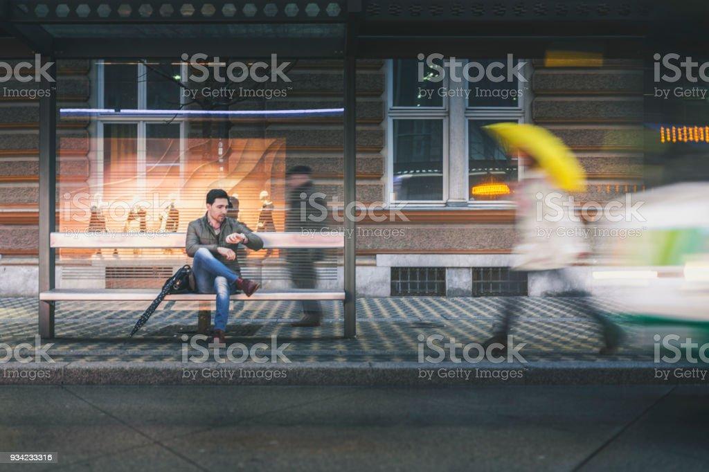 Mann an der Bushaltestelle an einem regnerischen Abend – Foto