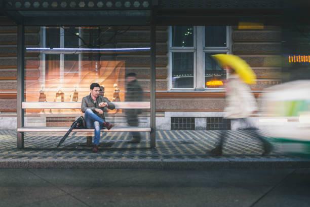 man op de halte op een regenachtige avond - bushalte stockfoto's en -beelden