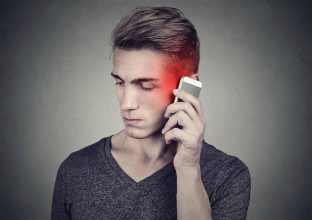 mann auf dem handy mit kopfschmerzen. verärgert unglücklich kerl telefonieren auf graue wand hintergrund isoliert. negative menschliche emotion gesicht ausdruck gefühl reaktion. - strahlung stock-fotos und bilder