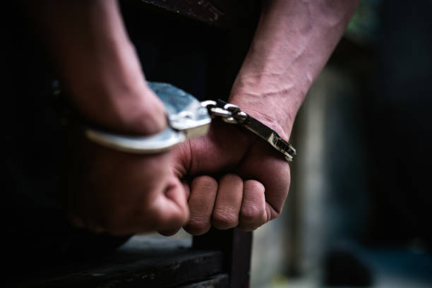 Man on the chair in Handcuffs. Rear view and Closeup Man on the chair in Handcuffs. Rear view and Closeup ,Men criminal in handcuffs arrested for crimes. With hands in back,boy  prison shackle in the jail violence concept. criminal stock pictures, royalty-free photos & images