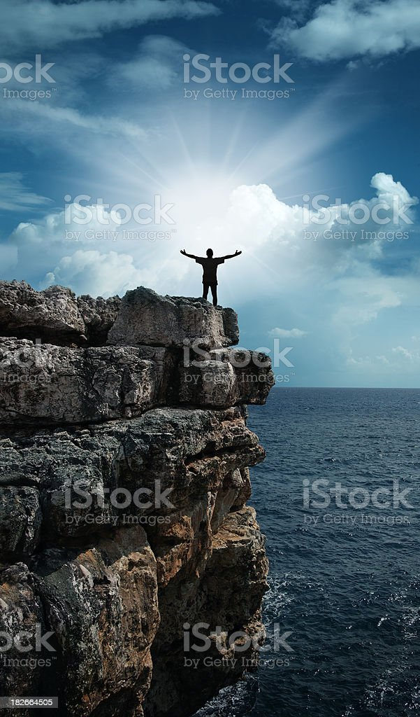 Man on the Cliff Worshiping Sun royalty-free stock photo