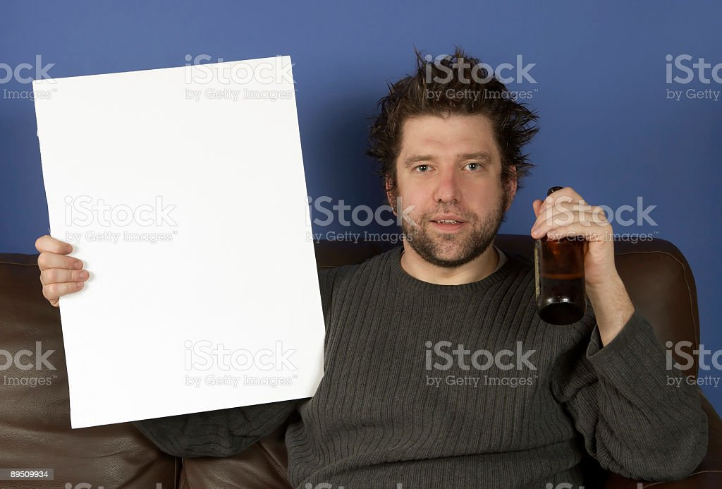Mann auf der couch halten einen leeren Schild Lizenzfreies stock-foto