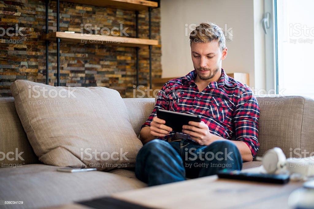 Homem no sofá, trabalhando em tablet digital foto royalty-free