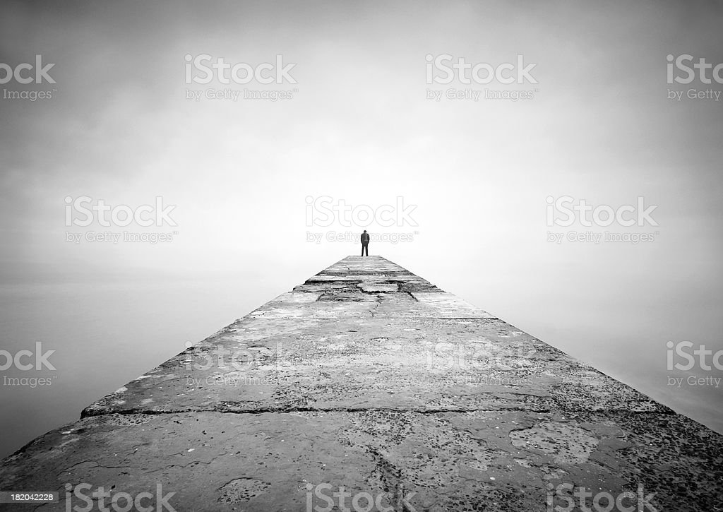"Man on the edge of pier ""Man is thinking on the edge of pier.  Image was shot with long exposure, therefore water looks in this way. Only man was pasted and horizon was removed, other on the photo is original. Man was pasted from another image"" Adult Stock Photo"