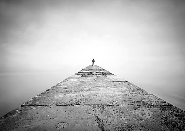 Man on the edge of pier stock photo