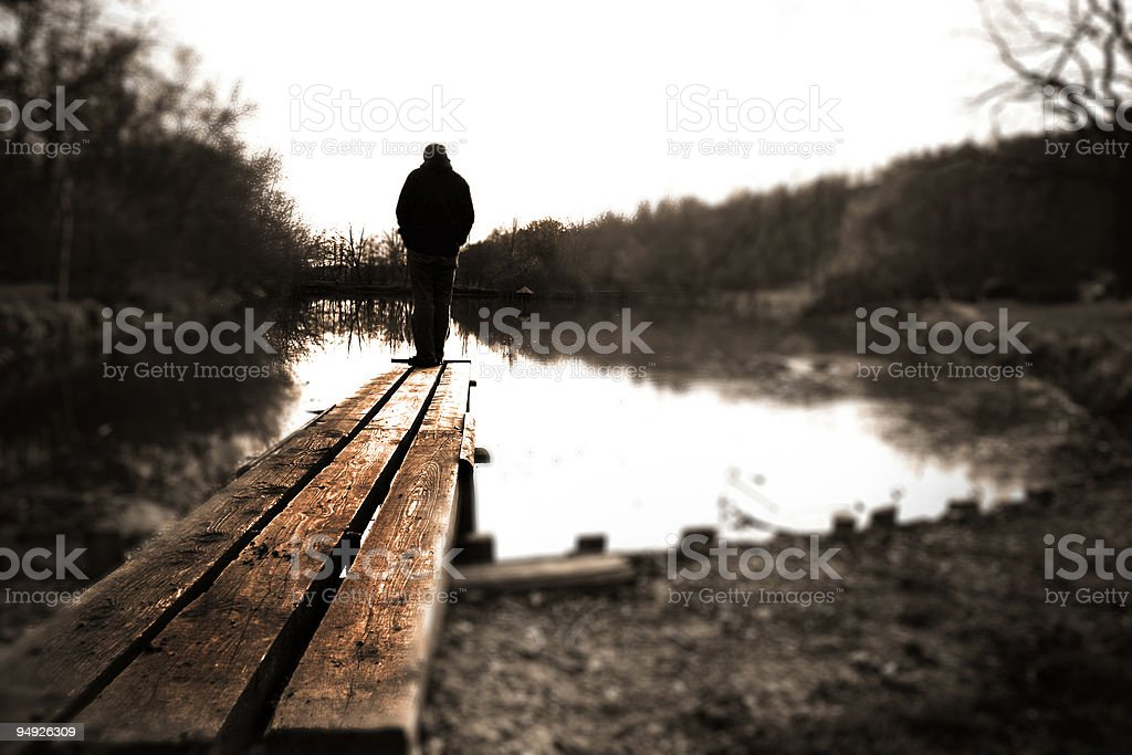 A man on the end of a pier by water royalty-free stock photo