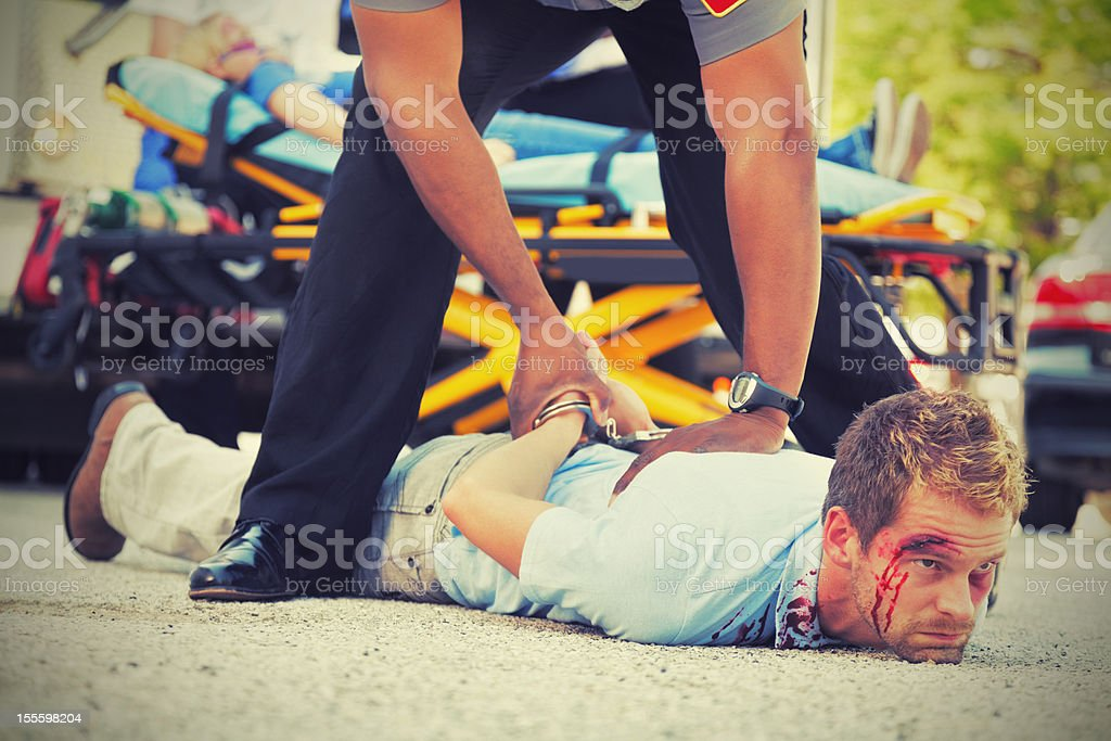 Man on the ground being arrested at crime scene royalty-free stock photo