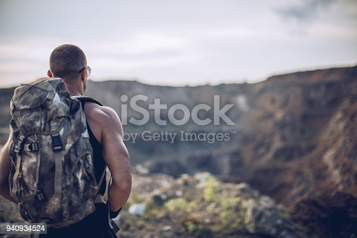 Rear view of a young athlete walking on the mountain path