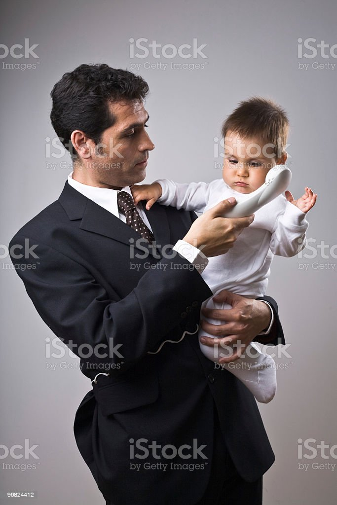 Man on the phone holding a baby royalty-free stock photo