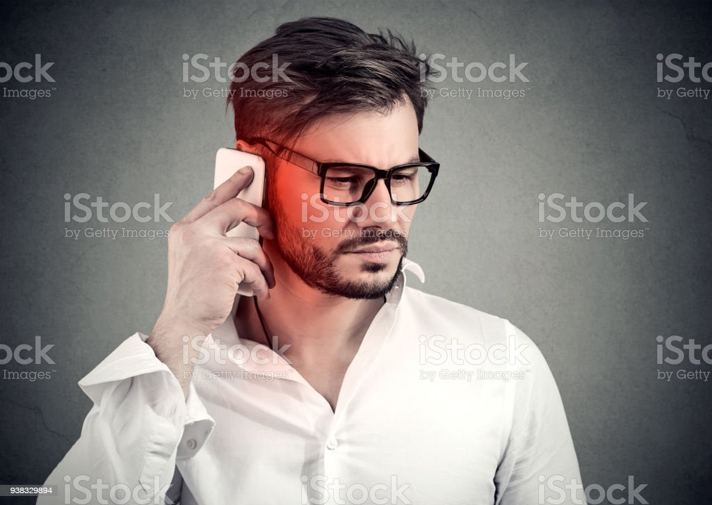 Man on the phone with headache. Upset unhappy guy talking on a cellphone stock photo