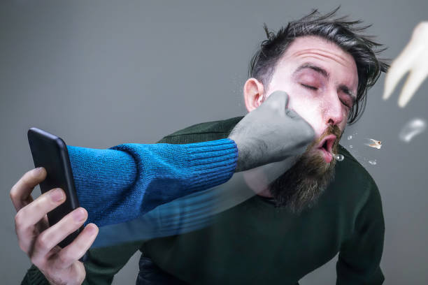 Man on the phone with one arm coming out of the phone and punching him in the face - foto stock