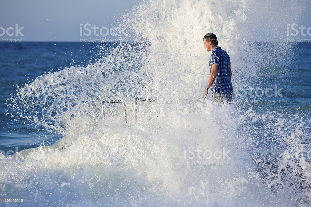 Man on the pier in splashes of big wave royalty-free stock photo