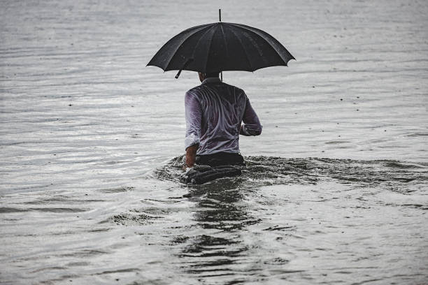 Man on the rain Rear view of a handsome adult man wearing white shirt and holding umbrella and briefcase, walking into the water near the river bank, during rainy day. The shot is executed with available natural light, and the copy space has been left. wading stock pictures, royalty-free photos & images