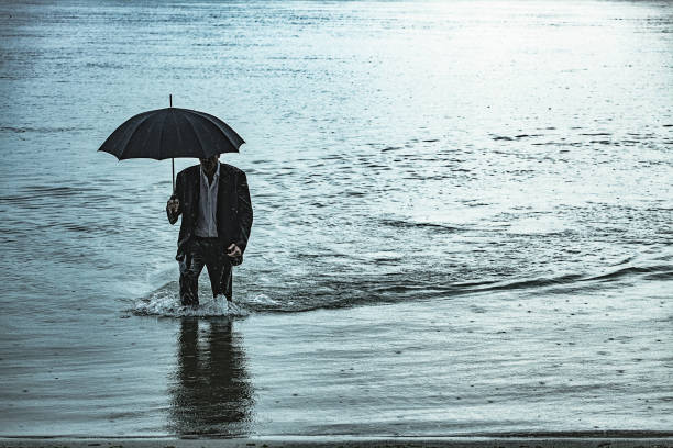 Man on the rain Adult man wearing full suit and holding umbrella and briefcase, comes out of the water near the river bank, during rainy day. The shot is executed with available natural light, and the copy space has been left. wading stock pictures, royalty-free photos & images