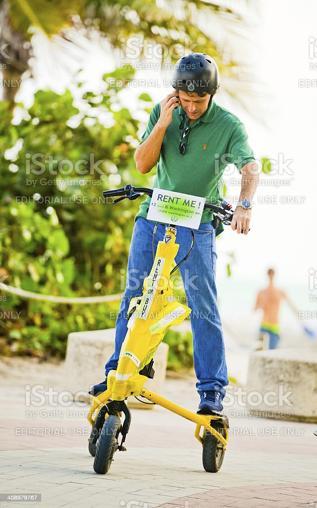 Man on the rented bike using mobile phone royalty-free stock photo