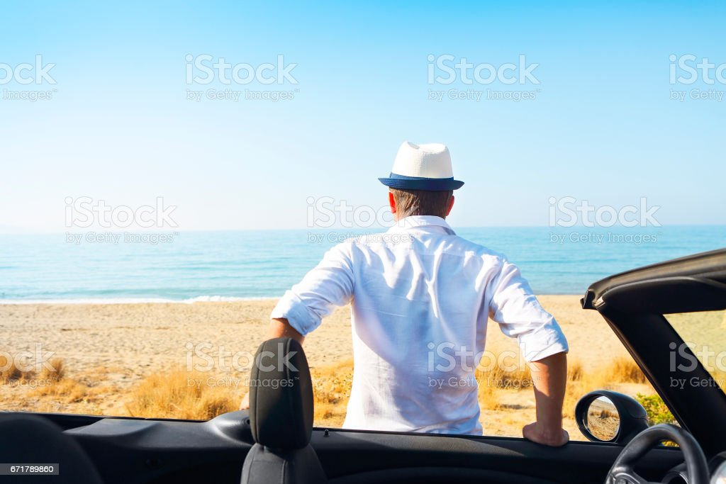 Man on the summer beach near car looking to the sea stock photo