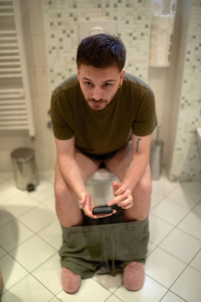 Man sitting on a toilet and looking in the cell phone. 4k