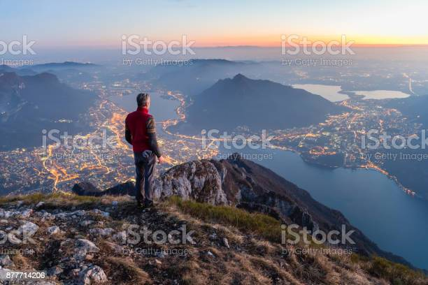 Photo of Man on the top of the mountain above the city