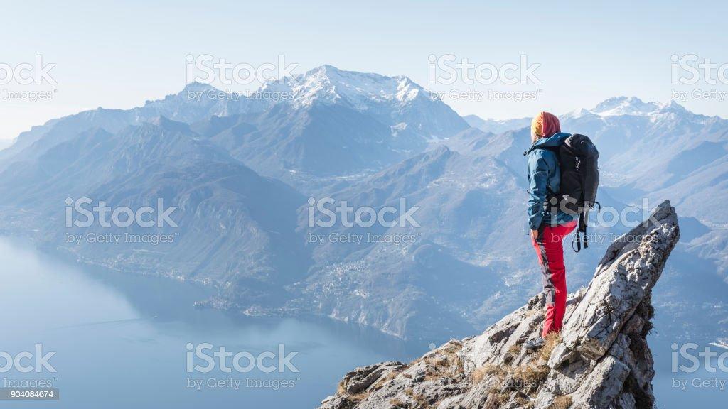 man on the top of the mountain peak stock photo