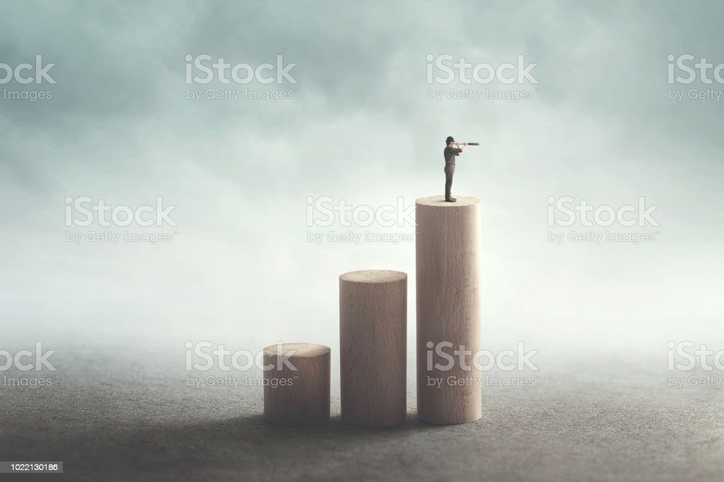 man on the top with binoculars observing the future stock photo