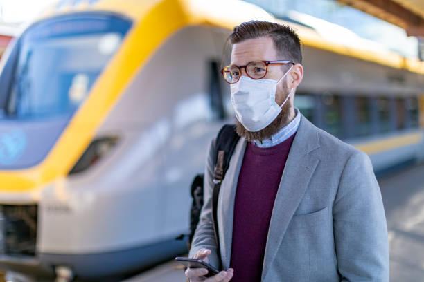ein mann auf dem bahnhof trägt schützende gesichtsmaske - ffp2 stock-fotos und bilder