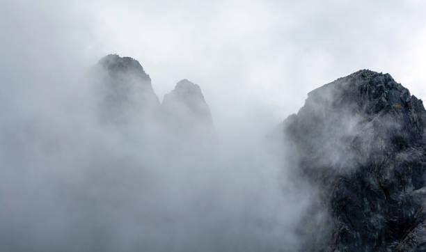 Mann an der Spitze. Landschaft von Berggipfeln umgeben von Wolken, die neben ihnen wirbeln. – Foto