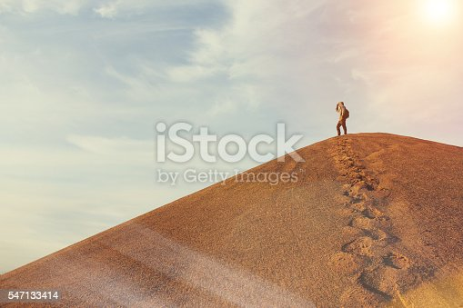 Man on top of a dune in the desert. Warm color