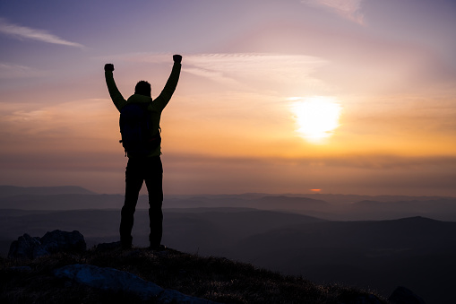 Rear view of a man's silhouette on top of a hill as he looks at the sun and valley with arms raised.