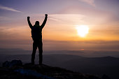 istock Man on top of a mountain looking at the sun with arms raised 1257438524