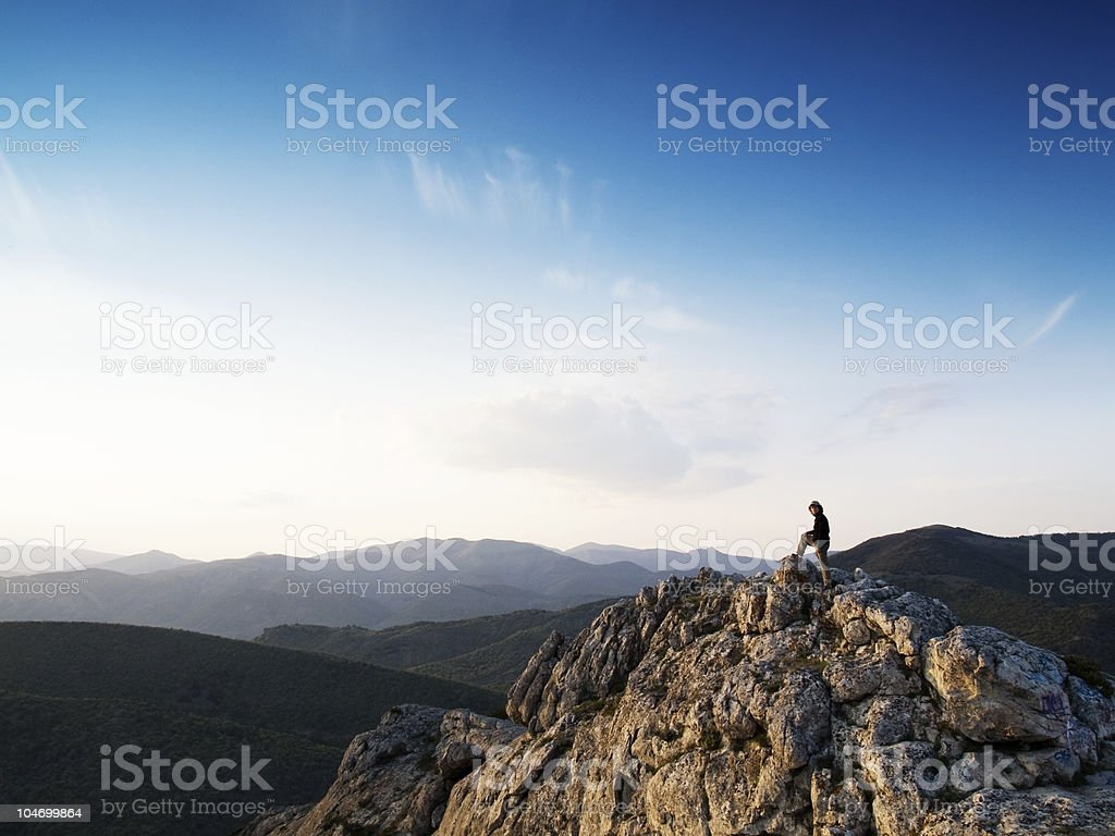 Man on top of a mountain looking over the world royalty-free stock photo