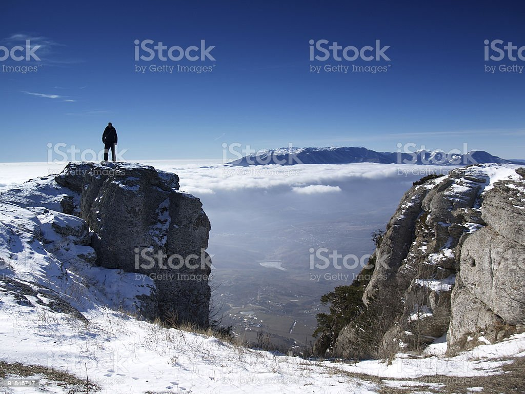Man on top of a snowy mountain range looking down below royalty-free stock photo