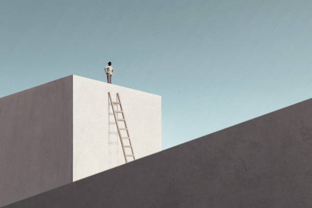 man on top of minimalist structure observing the sky stock photo