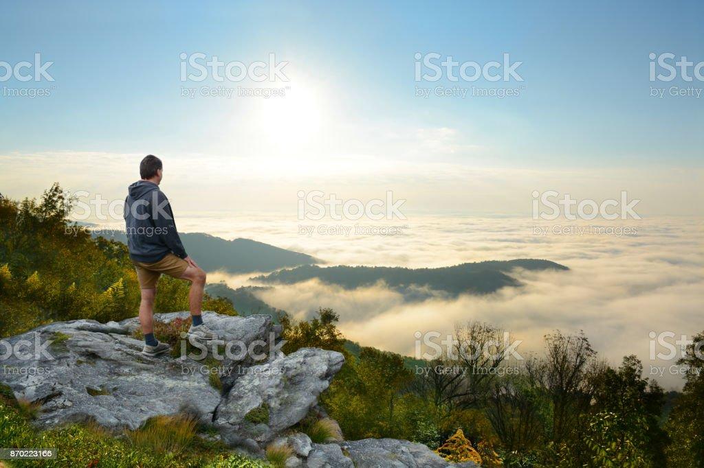 Man on top of mountain enjoying  beautiful foggy mountain landscape at sunrise. stock photo