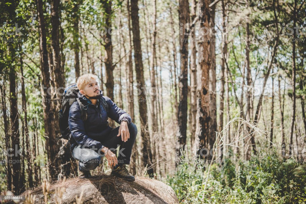 Man on top of mountain sitting on the rock watching a nice nature around. Men lifestyle concept. stock photo