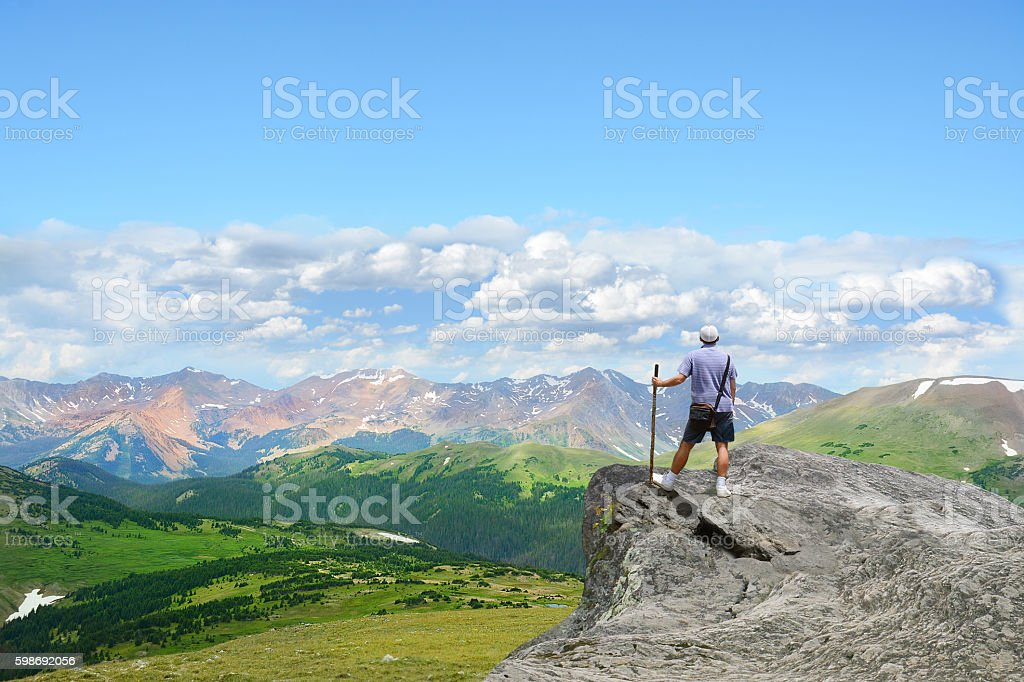 Man on top of the mountain looking at beautiful view. stock photo