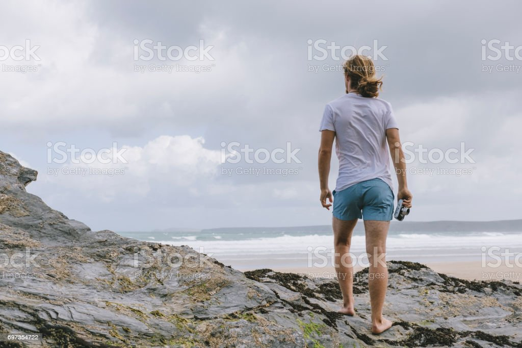 Man on Towan Beach, Newquay, holding an old film camera. stock photo