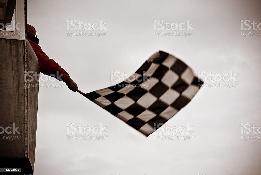 Man on tower waving checkered flag royalty-free stock photo