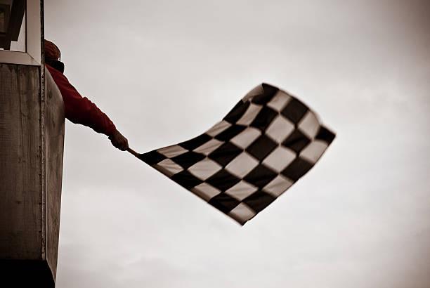 Man on tower waving checkered flag stock photo