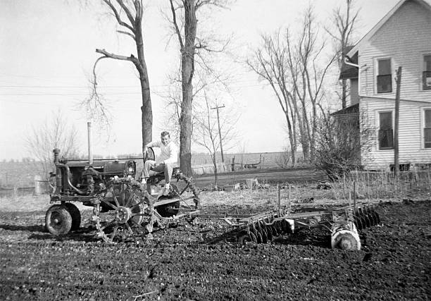 man on tractor disking 1941, retro Man on tractor disking. Metal wheels on tractor. Wellman, Iowa, USA. 1941. Scanned film with grain. war effort stock pictures, royalty-free photos & images