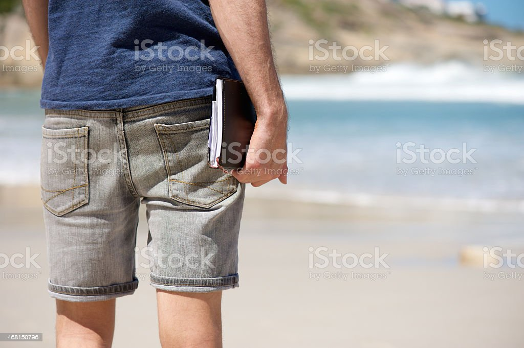 Man on vacation holding diary book at the beach stock photo