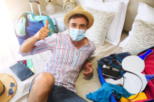 Man on vacation in room protected with mask ok gesture stock photo