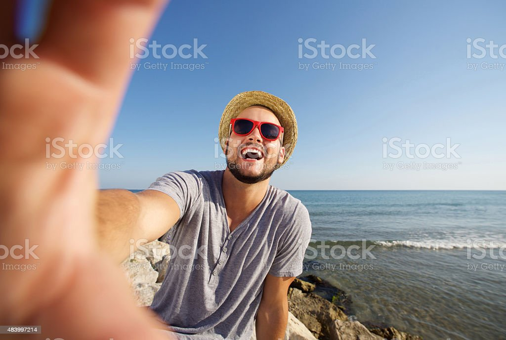 Man on vacation laughing at the beach taking selfie stock photo