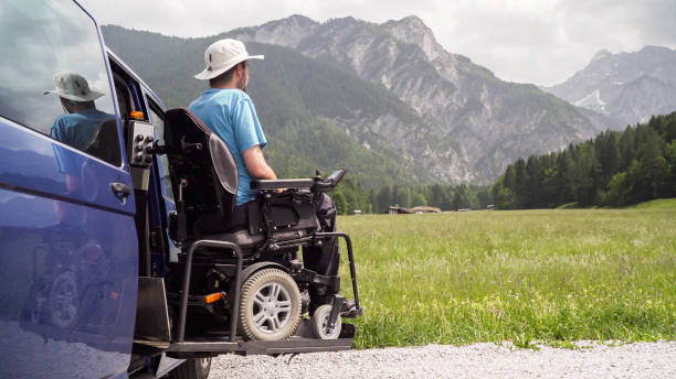 man on wheelchair going out of a car on electric lift specialized vehicle for people with disabilities. Self help for disabled people concept stock photo