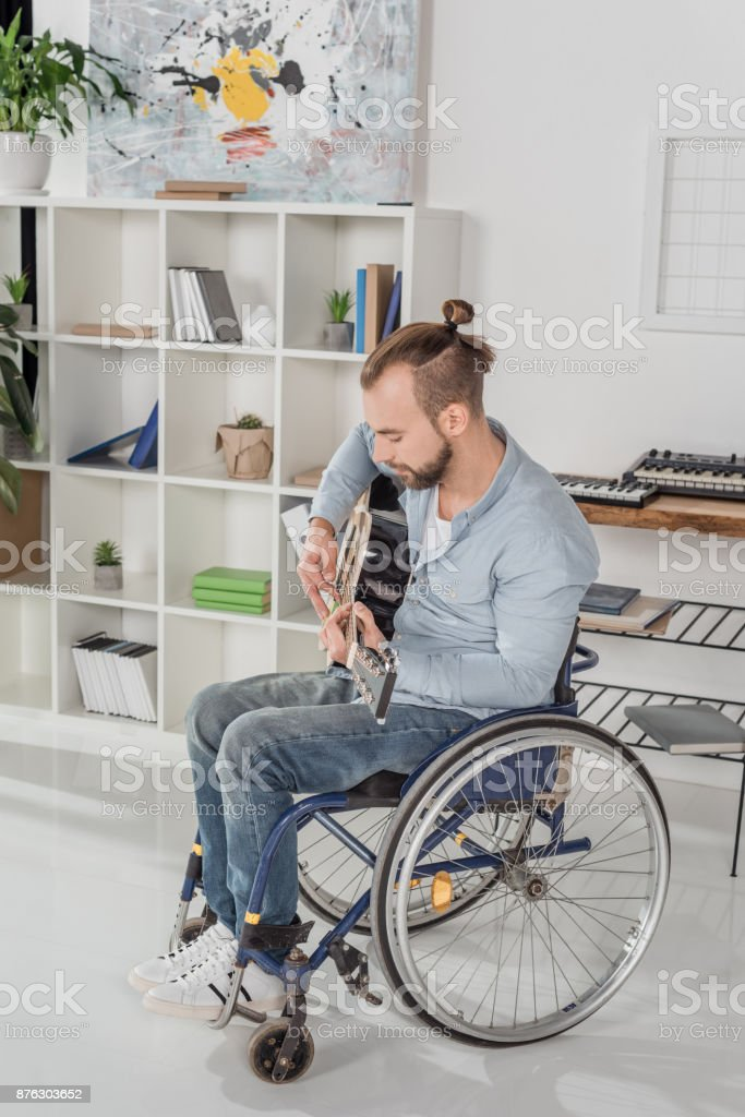 man on wheelchair playing guitar stock photo