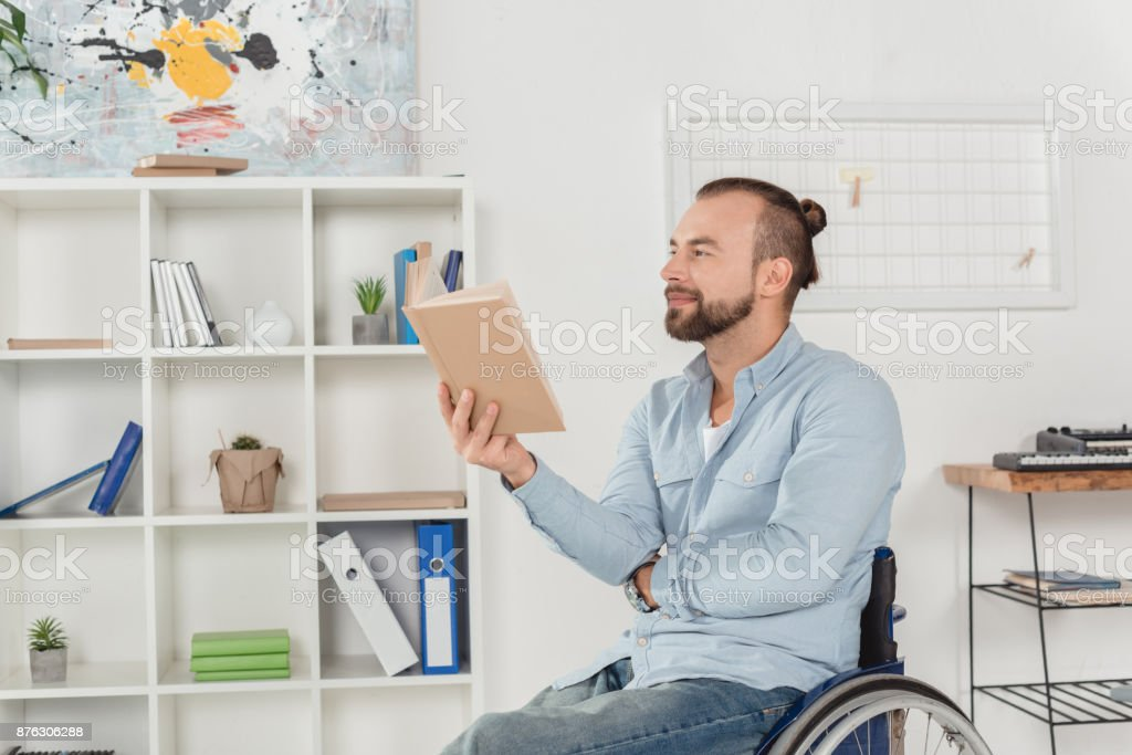 man on wheelchair reading book stock photo
